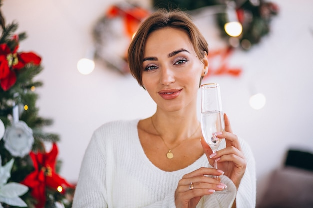 Woman drinking champaigne by christmas tree Free Photo