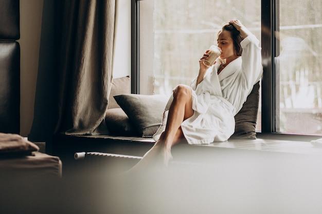 Caffè bevente della donna in accappatoio dalla finestra a casa Foto Gratuite