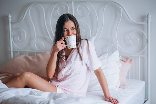 Woman drinking coffee in bed Free Photo