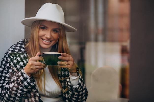 Donna che beve il caffè in un bar, seduto dietro il vetro Foto Gratuite