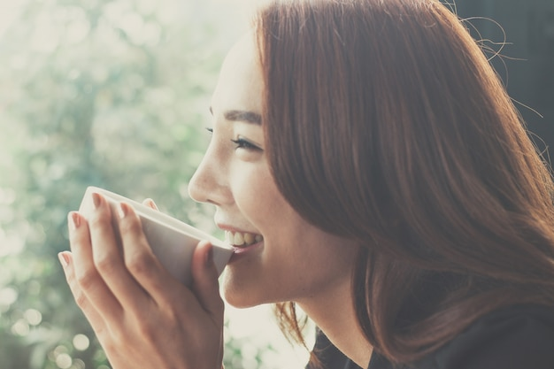 Woman drinking coffee at a coffee shop,secretaries are happy when they drink coffee. Premium Photo