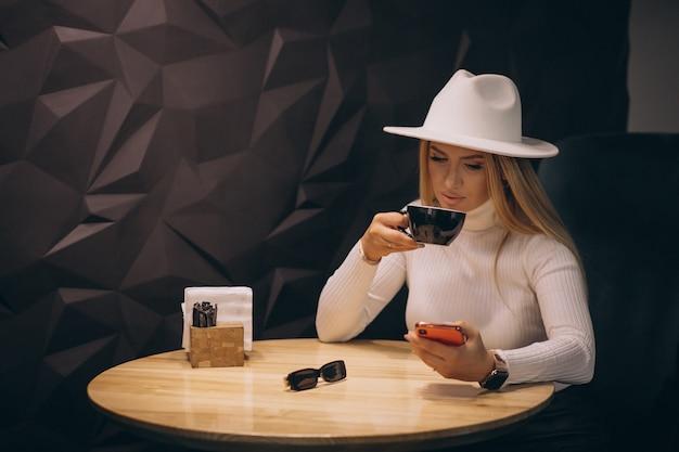 カフェでコーヒーを飲み、電話で話している女性 無料写真