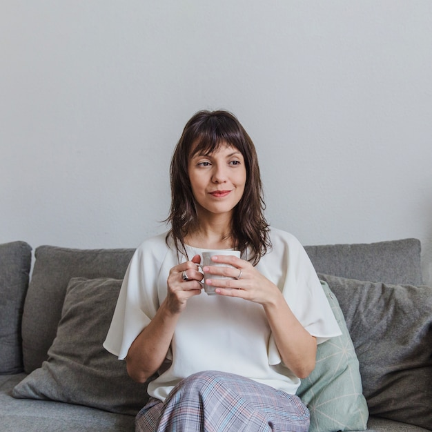 Woman drinking coffee on sofa Free Photo