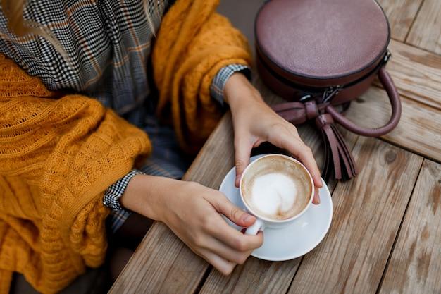 Женщина пьет кофе. стильная сумка на столе. в сером платье и оранжевой клетке. наслаждаемся уютным утром в кафе. Бесплатные Фотографии