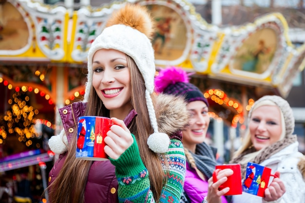 Woman drinking eggnog on german christmas market Premium Photo