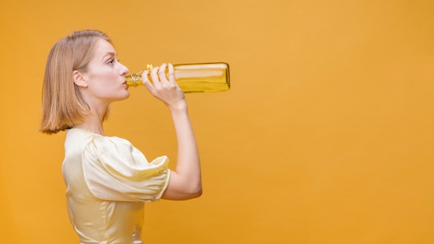 Woman drinking from bottle in a yellow scene Free Photo
