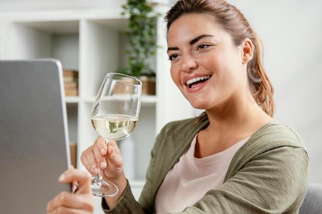 Donna che beve un bicchiere di vino durante l'utilizzo di laptop Foto Gratuite