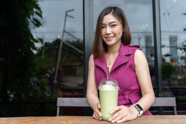 Woman drinking green tea frappe in cafe Premium Photo