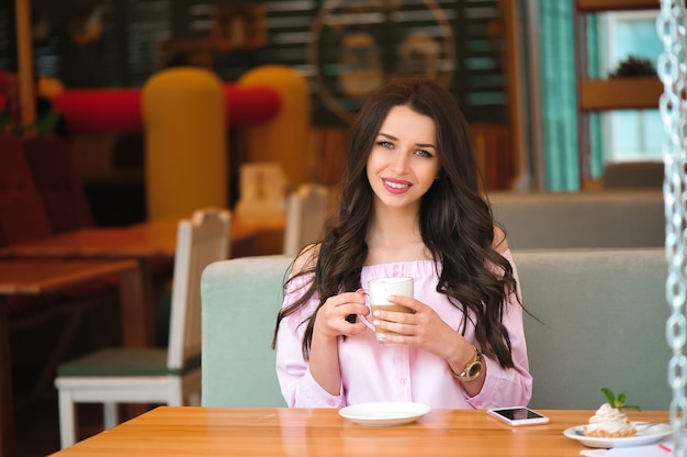 Woman drinking hot cappuccino coffee and eating cake at a cafe. Premium Photo