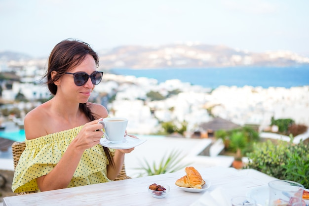 Woman drinking hot coffee on luxury hotel terrace with sea view at resort restaurant. Premium Photo