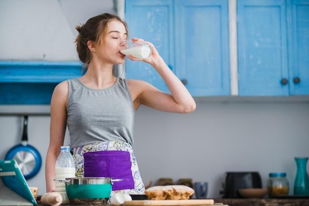 Woman drinking milk in kitchen Free Photo