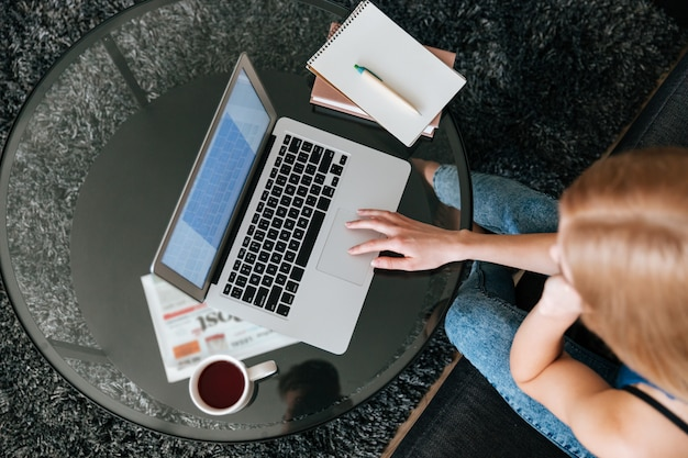 Woman drinking tea and using laptop at home Free Photo