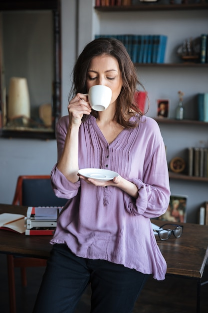 自宅のテーブルにもたれながらお茶を飲む女性 無料写真
