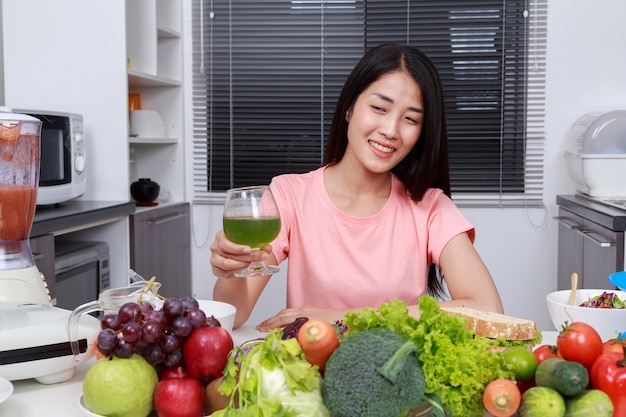 Woman drinking vegetable juice in kitchen Premium Photo