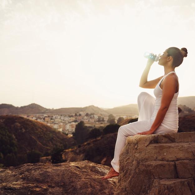 Acqua potabile della donna dopo lo yoga Foto Gratuite