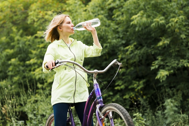 Woman drinking water on bicycle Free Photo