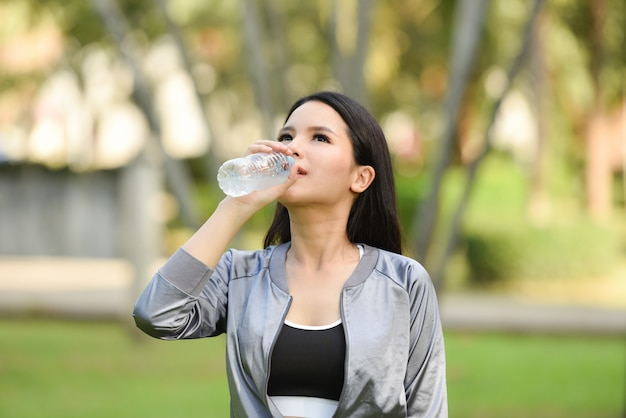 Woman drinking water bottle health concept smiling young girl relax Premium Photo
