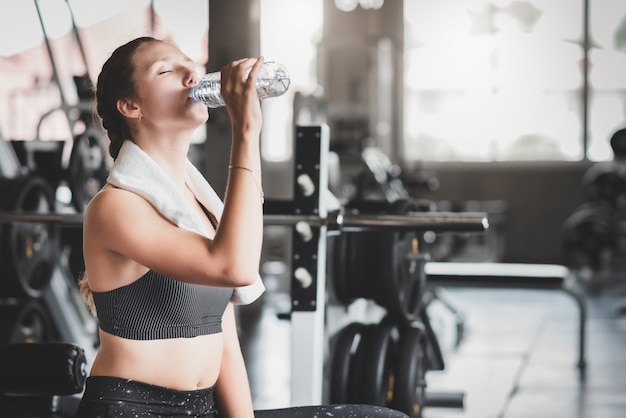 Woman drinking water from bottle after workout Premium Photo