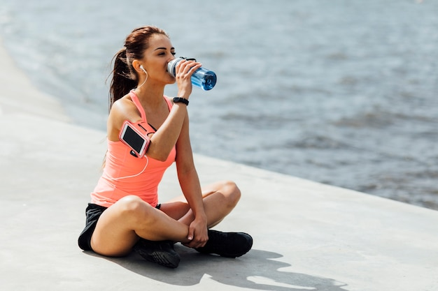 Woman drinking water from a bottle Free Photo