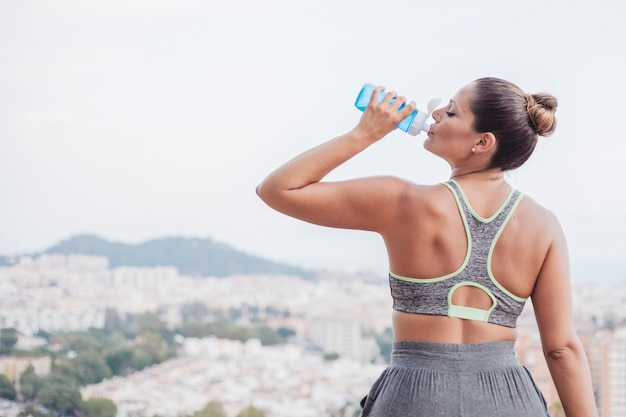 Woman drinking water in front of city Free Photo