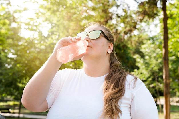 Женщина пьет воду в парке Бесплатные Фотографии