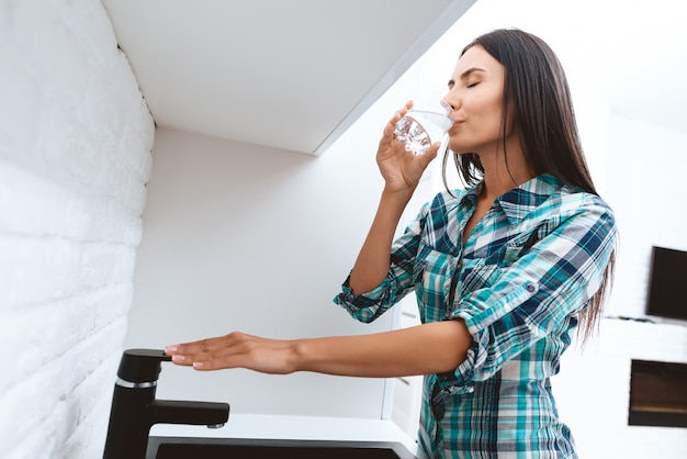 Woman drinks water from glass. hand on a tap. Premium Photo