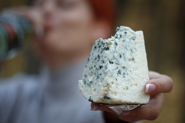 Woman drinks wine from a bottle and holds in her hand a large bitten piece of cheese Premium Photo