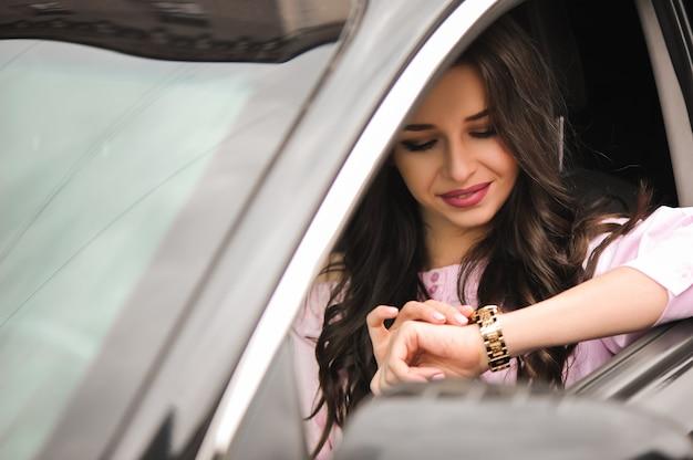 車を運転して時計を見て女性 Premium写真