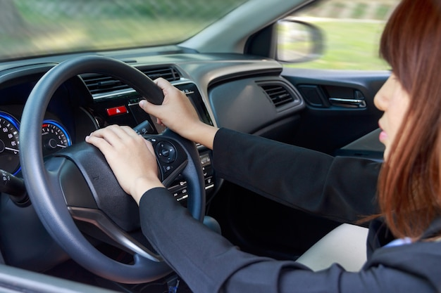 Woman driving a car and pressing on horn button - transportation concept. Premium Photo