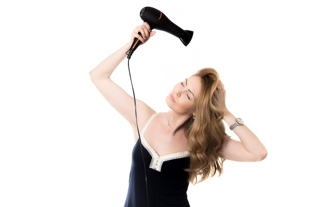 Woman drying her hair  with a blow dryer Free Photo