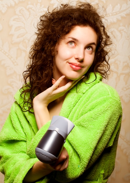 Woman drying her hair with hairdryer Premium Photo
