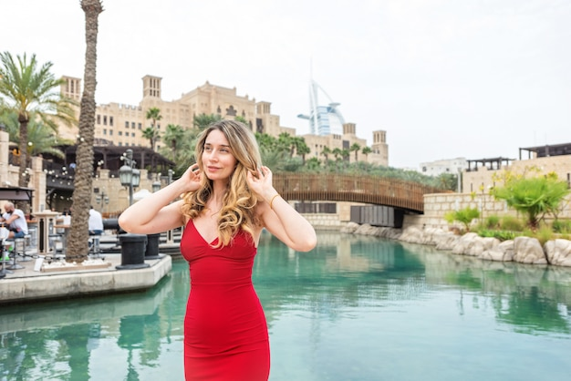 Woman in dubai, united arab emirates. attractive lady wearing a red dress. girl admiring the city views Premium Photo