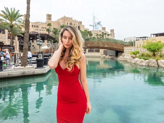 Woman in dubai, united arab emirates. attractive lady wearing a red dress. sad mood lonely feelings Premium Photo