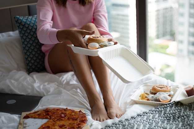 自宅の寝室のベッドで配達から女性東ファーストフード 無料写真