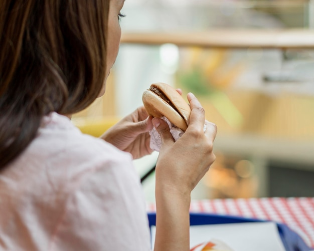 レストランでハンバーガーを食べる女性 無料写真