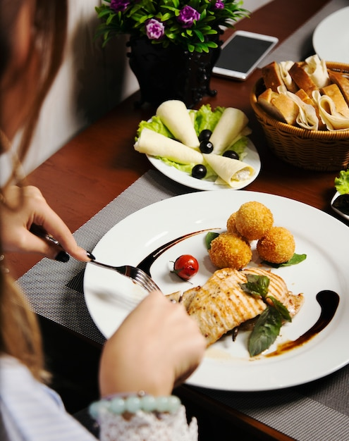 Woman eating baked salmon fillet with potatoes and cheese rolls, and vegetables mix. Free Photo