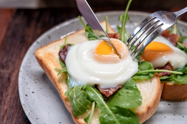 A woman eating breakfast sandwich with eggs, bacon and sour cream by knife and fork in a plate on wooden table Premium Photo