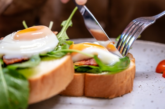 A woman eating breakfast sandwich with eggs, bacon and sour cream by knife and spoon in a plate on wooden table Premium Photo