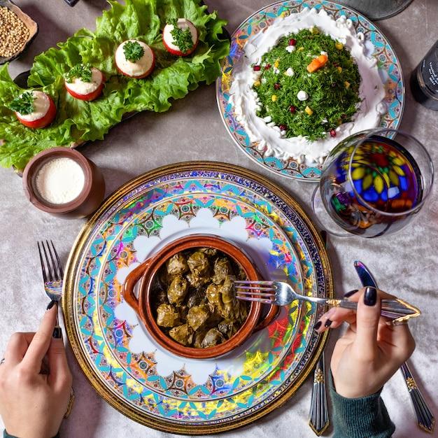 Женщина ест долму, вид сверху азербайджанской еды Premium Фотографии