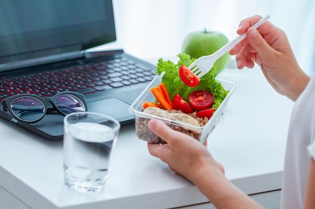 점심 시간 동안 직장에서 도시락 상자에서 음식을 먹는 여자. 직장에서 컨테이너 식품 프리미엄 사진