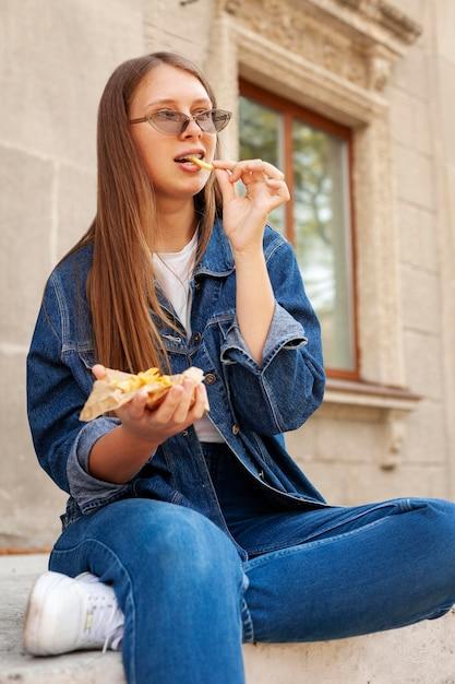 Женщина ест картофель на открытом воздухе Бесплатные Фотографии