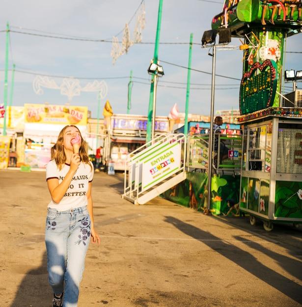 Woman eating ice cream at amusement park Free Photo