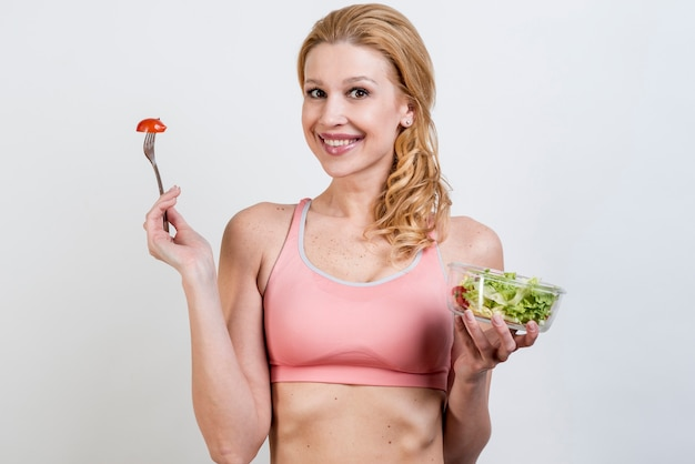 Woman eating a lettuce salad Free Photo