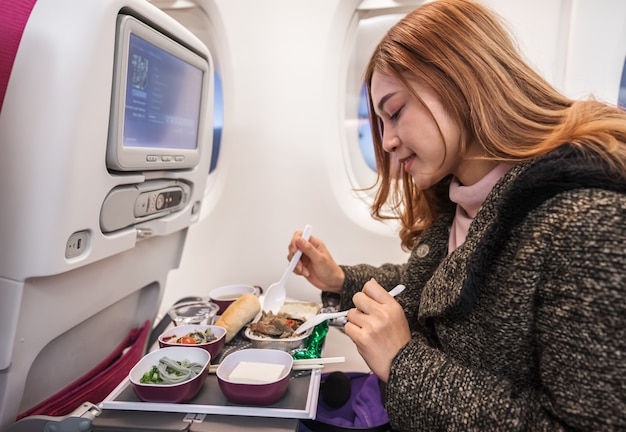 Woman eating meal on commercial airplane in flight time. Premium Photo