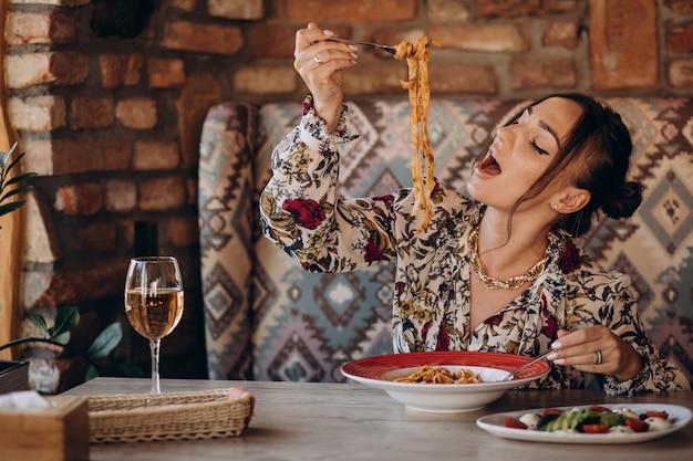 Женщина ест пасту в итальянском ресторане Бесплатные Фотографии