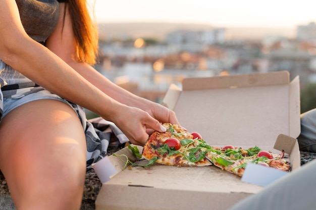 Woman eating pizza outdoors Free Photo