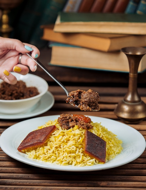Woman eating traditional govurma plov with a spoon. Free Photo