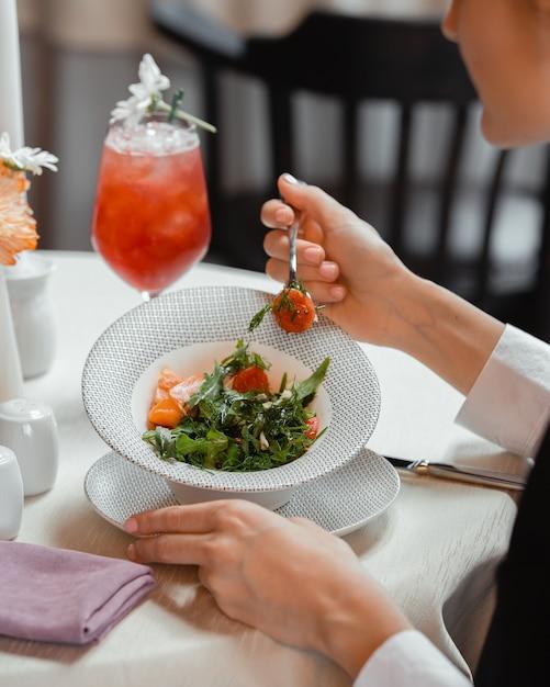 Женщина ест овощной салат с помидорами, болгарским перцем, укропом и рукколой Бесплатные Фотографии