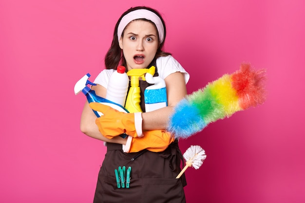 Woman embraces lots bottles of detergent, pp duster, dressed in white t shirt, brown apron, hairband Free Photo