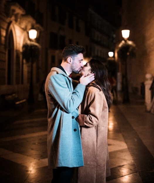woman embracing and kissing with young man on promenade in evening
